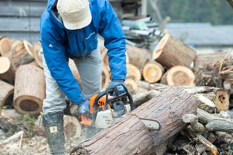 チェーンソーで材木を伐る井上さん