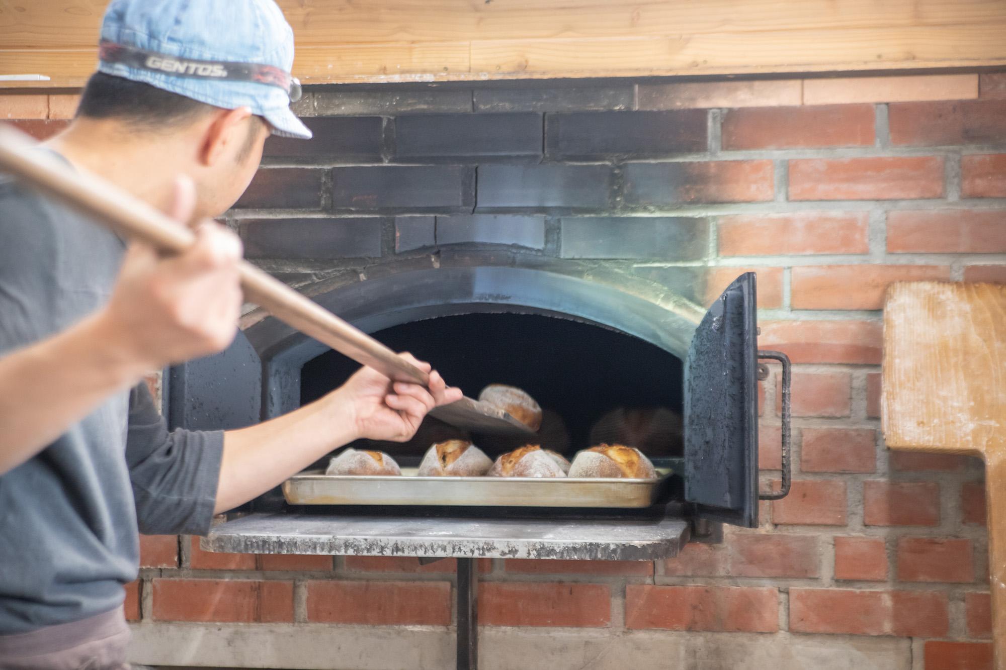窯からパンを出す井上さん